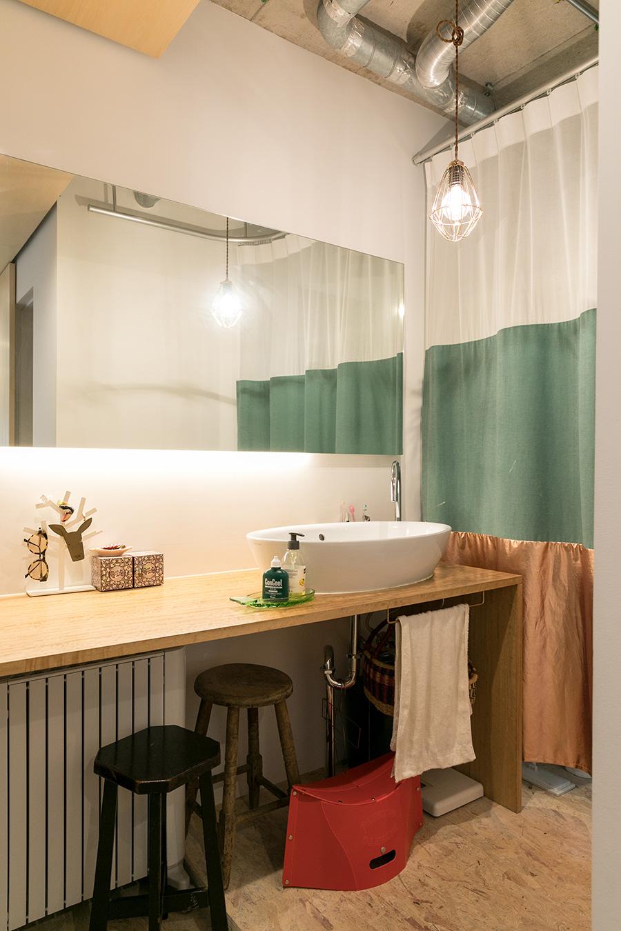 洗面所や寝室は、安東陽子さんデザインのテキスタイルで柔らかく仕切られる。「洗面ボウルは、いろいろ比較検討した結果、この丸いカタチのものにしました」