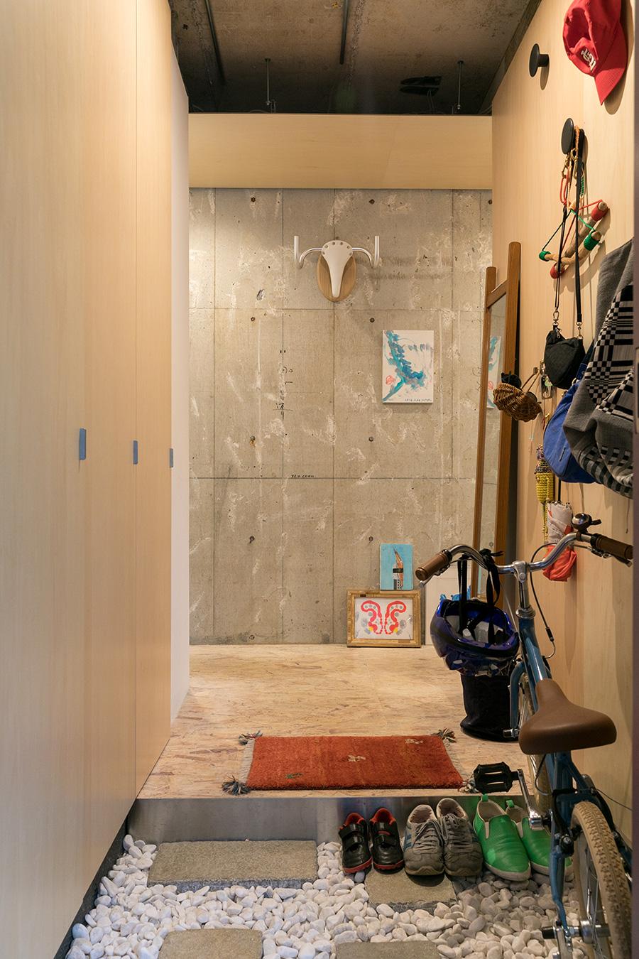 """「実家に帰った時に近所のホームセンターで買った玉砂利を玄関に敷きました」 正面のサドルとハンドルで作ったオブジェは賢策さんの""""日曜アート""""だそう。右の壁の丸いフックは後から賢策さんが取付けた。"""