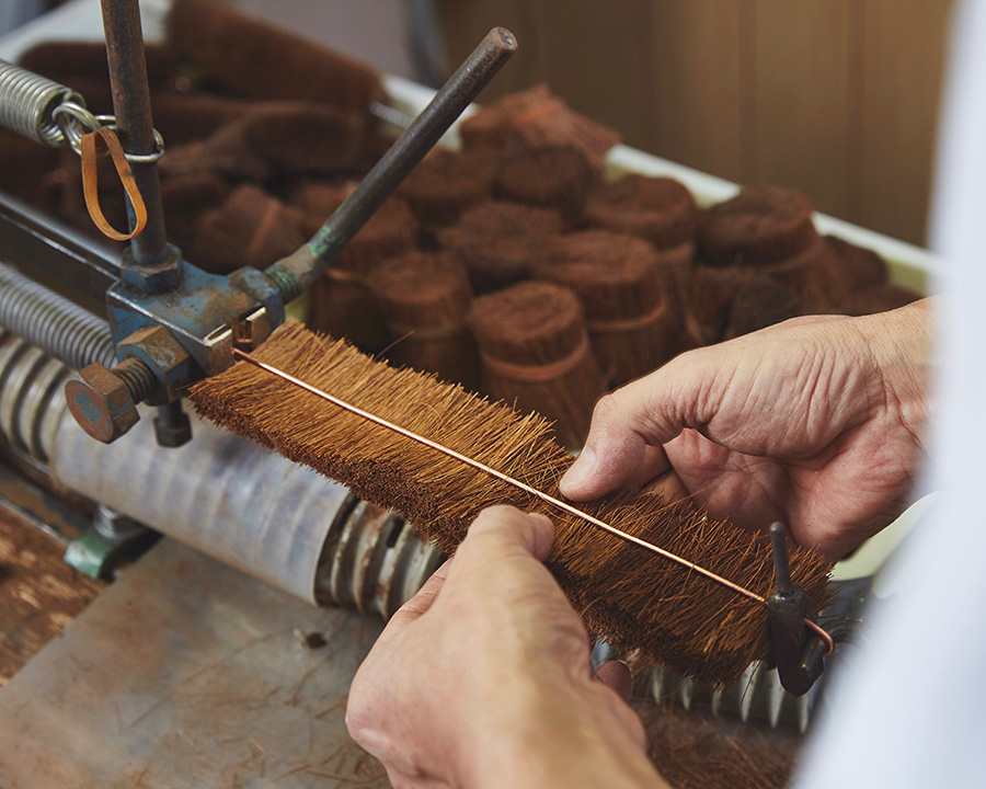 棕櫚繊維をたわし巻き機にセットされた針金に均一に挟む。