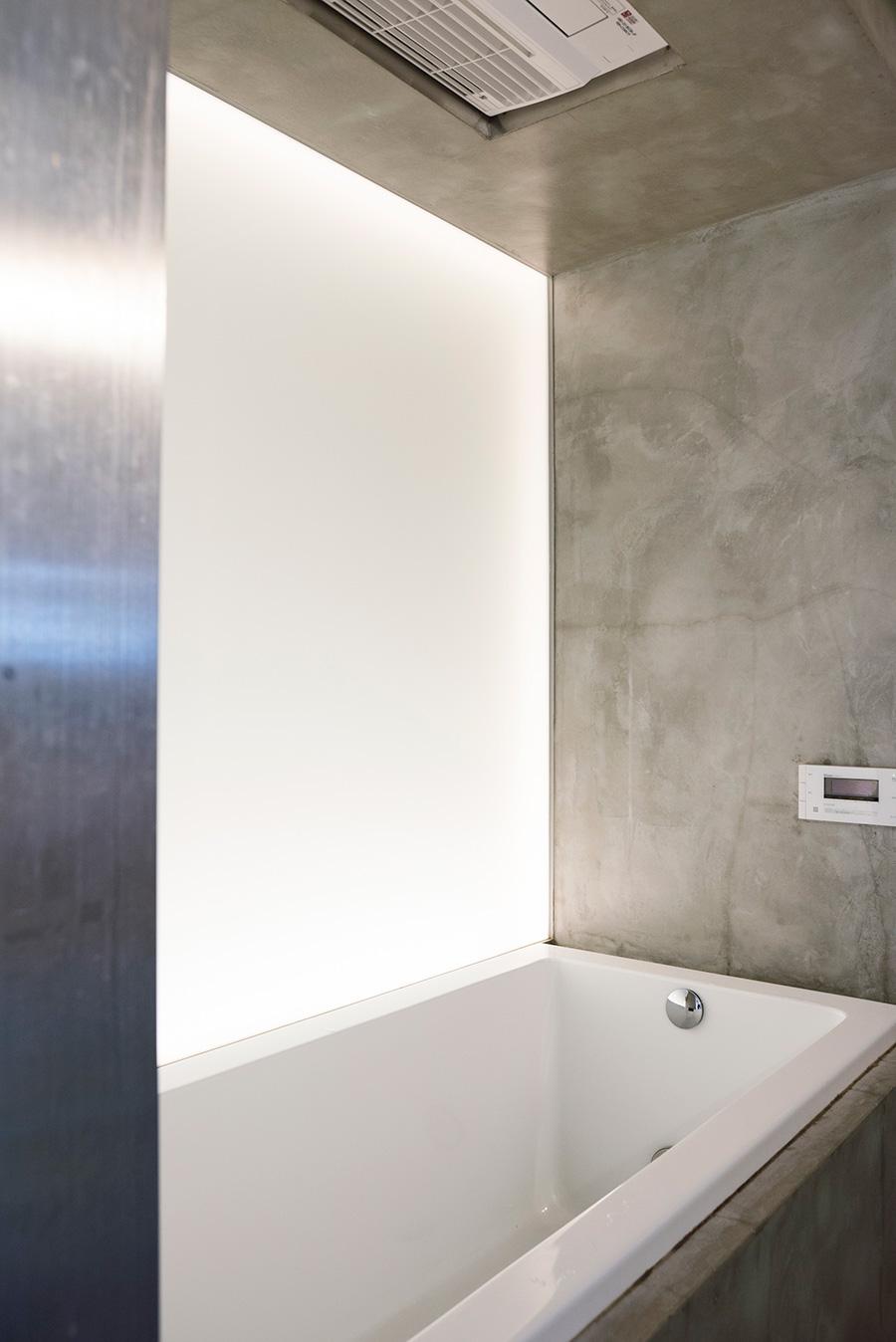 モルタルのモダンでクリーンなバスルーム。配管のあった壁側は内照式の壁として、窓のない浴室に柔らかい光を作り出す。