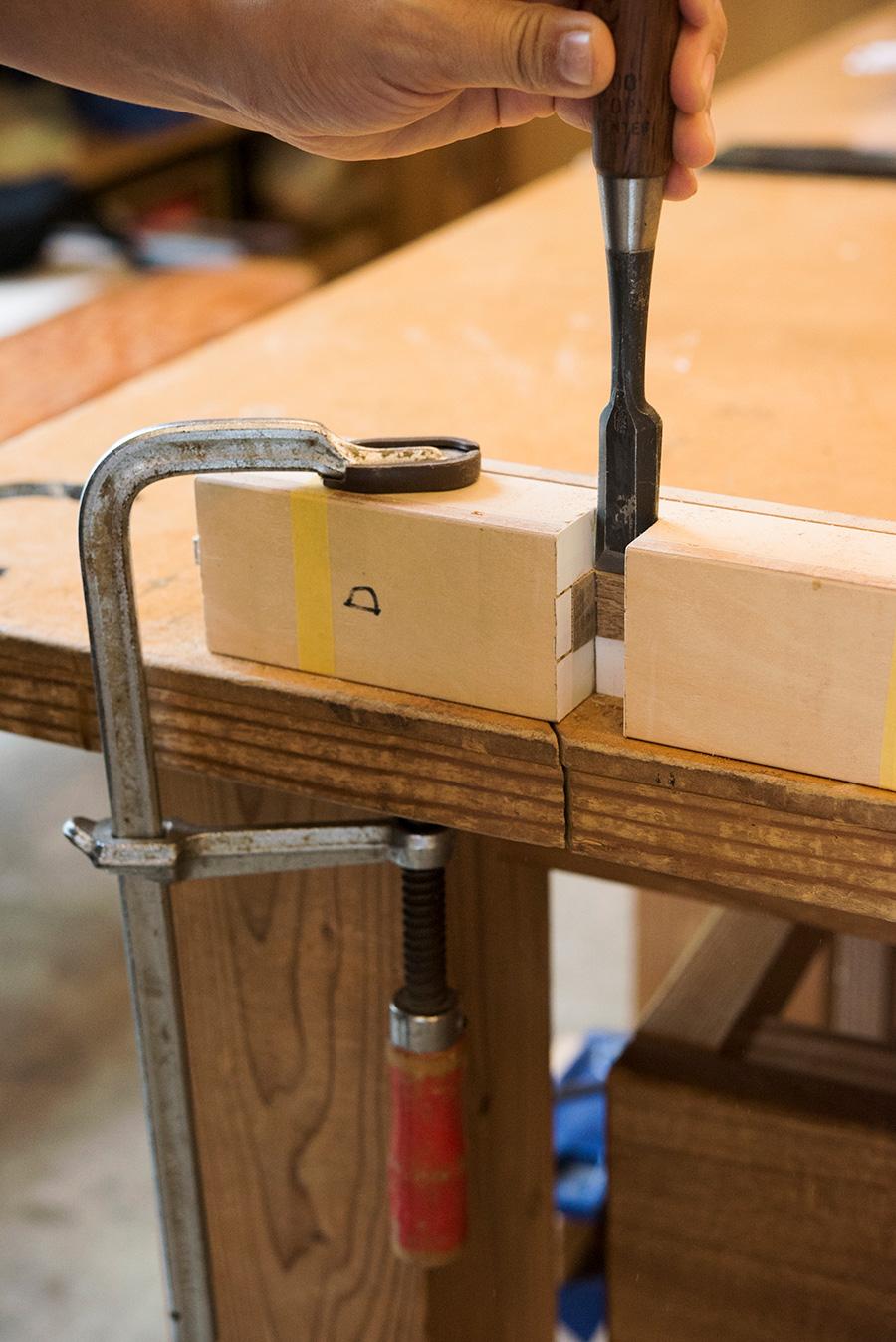 Fクランプをテーブルに固定し、「貫」の中央の接合部「相欠き」を、玄能とノミで欠き取る。