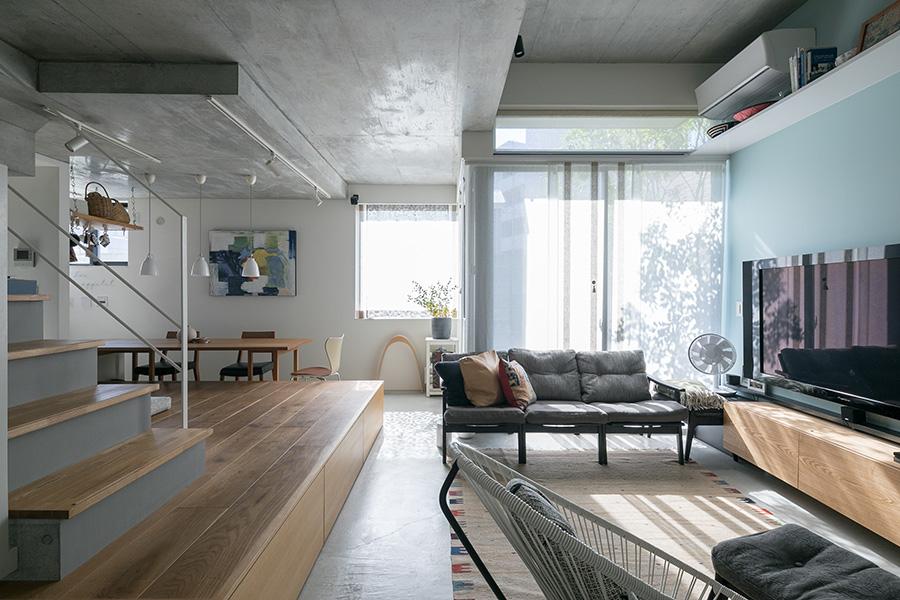 玄関からダイニングスペースを見る。右上の天井は少し高めに。L字型の窓が心地よい動線を生む。