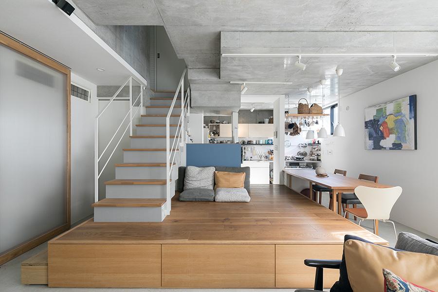 リビングスペースからキッチンを見る。小上がりの縁は腰掛けるのにちょうど良い高さ。椅子がなくても大人数に対応できる、集まれる空間にも。