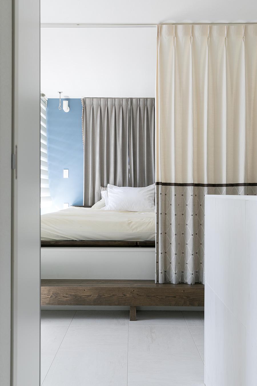 2階寝室。小さなベランダから明るい光が差し込む。この部屋の手前に収納と洗濯干しスペースがある。天井高さは低いとはいえ、落ち着きの出る空間になっている。