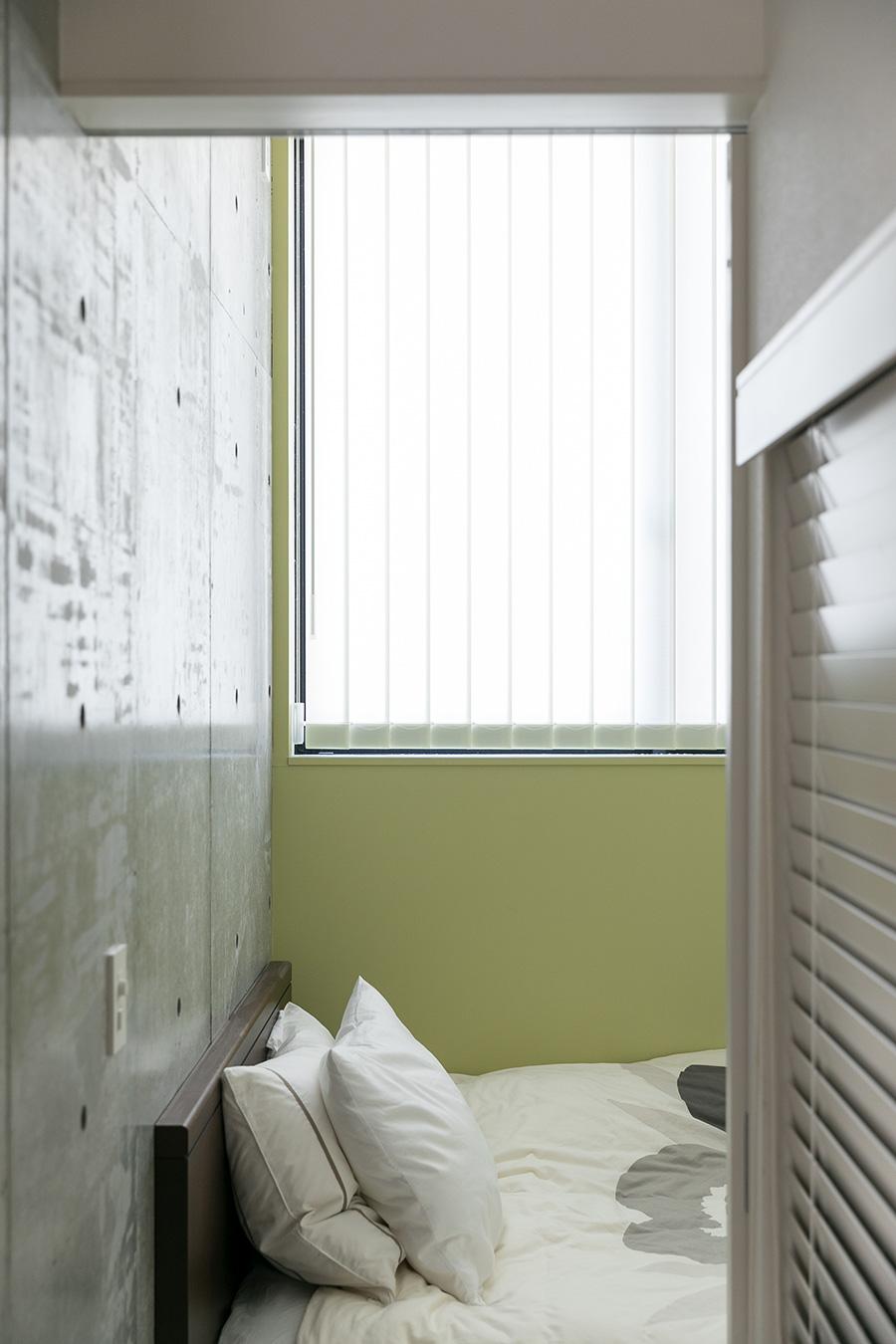二階の寝室。壁は薄いグリーンの塗装でコンクリートに温かみを与えている。