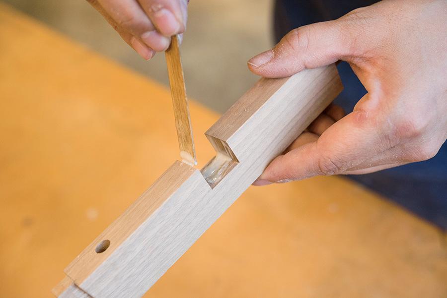 タイトボンドを貫の相欠きのところの接着面につけ、ヘラを使って均一にならしていく。