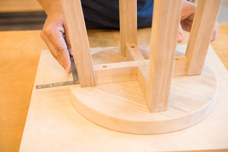 脚に座面を取り付ける。裏側にして直角の定規を当て、同じ長さをとって脚の位置を中心に合わせる。