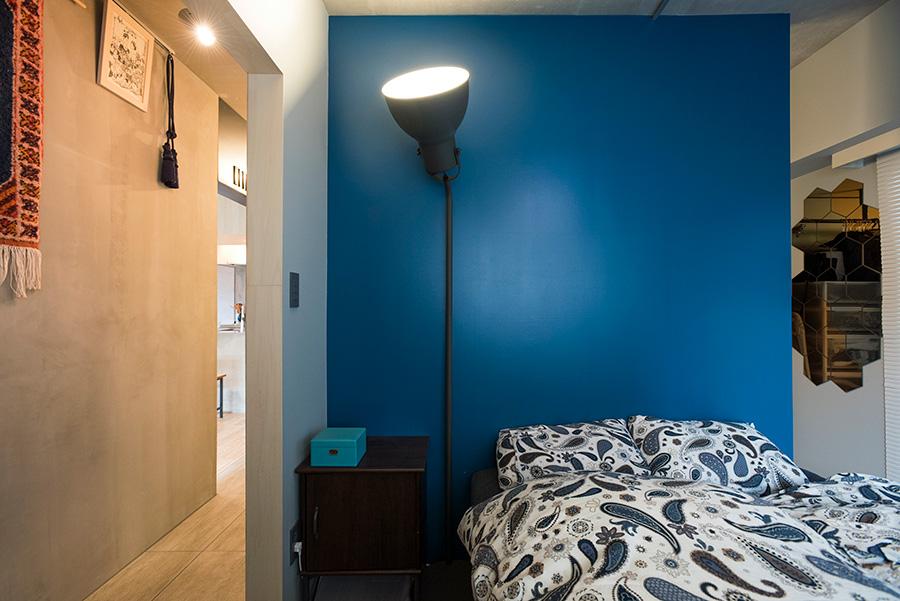 ベッドルームにも扉はなく、クローゼットを仕切る壁のみ。クローゼットをまわり込んで、左右どちら側からも入れるようになっている。壁は真実さんの希望で青く塗装。廊下、玄関側の床には色ムラのある磁器タイルを使い、LDKと雰囲気を切替えている。