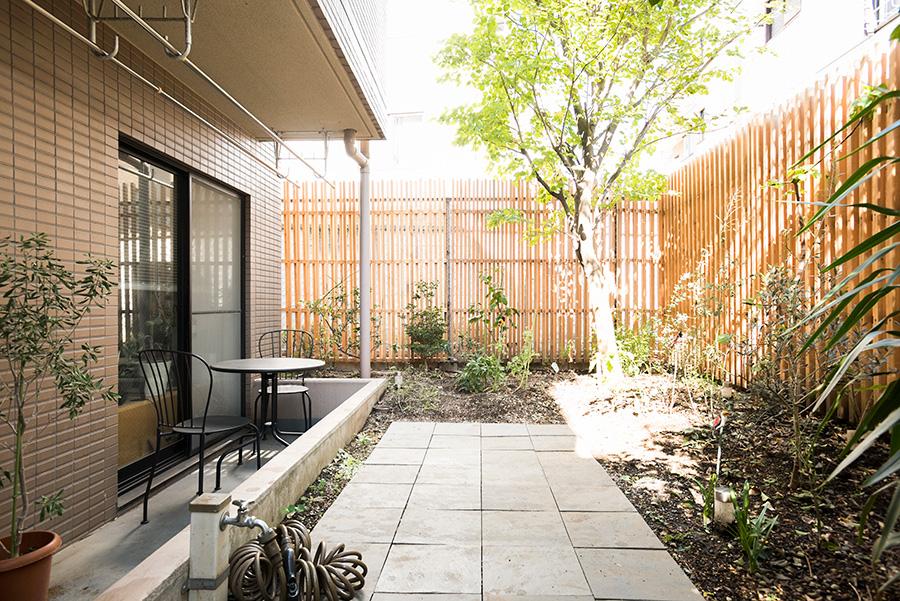 専用庭はDIYでタイルを貼り柵を設けた。サンショウ、イチジク、ブルーベリーなど実ものを育てる。