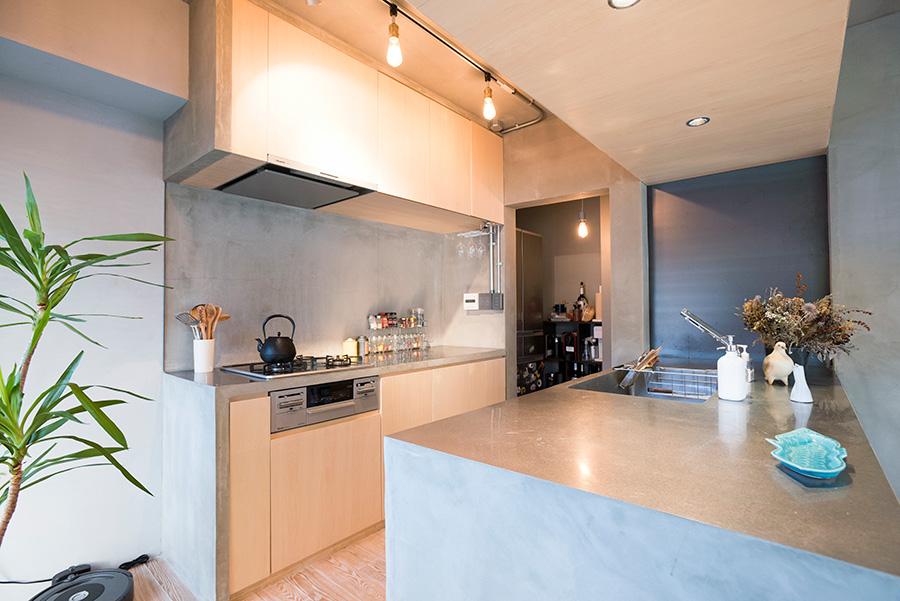 「キッチンカウンターは壁にあけた穴に突き刺さっている感じにしたかった」と、奥の壁をあえて凹ませ、黒皮鉄をあしらった。モルタルにステンレス天板のカウンターに、コンロ側のシナ合板の面材がやわらかな雰囲気を添える。