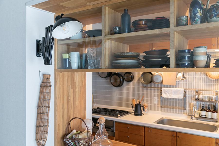 独立型だったキッチンの壁を取り払い、上の棚はガラスをはめて、両サイドから器のコレクションを楽しめるようにした。左側に飾った籠はうなぎを捕るためのもの。