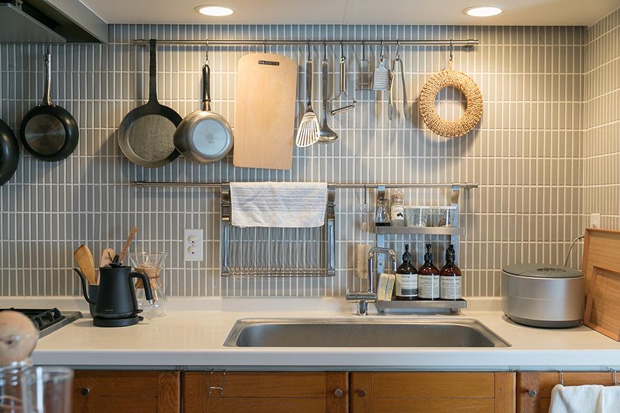 「キッチンのリノベーションは、壁と床にタイルを貼り、コンロを替えて、棚の一部を取り払いました」