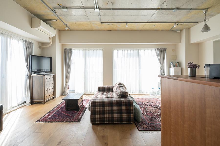 ひと部屋にしたリビングスペースはソファでゆるやかに仕切っている。十分すぎる採光が魅力で、カーテンの向こうには見晴らしのよい景色が広がっている。