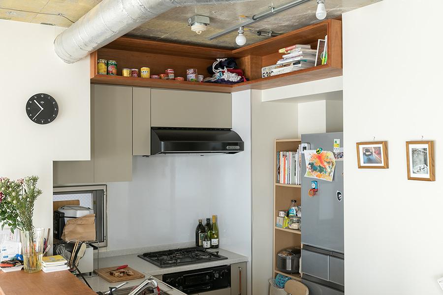 キッチンはコンパクトだが使いやすい動線。天井を貼らなかったことでできたスペースに造作収納をつけ、非常食などを置いている。