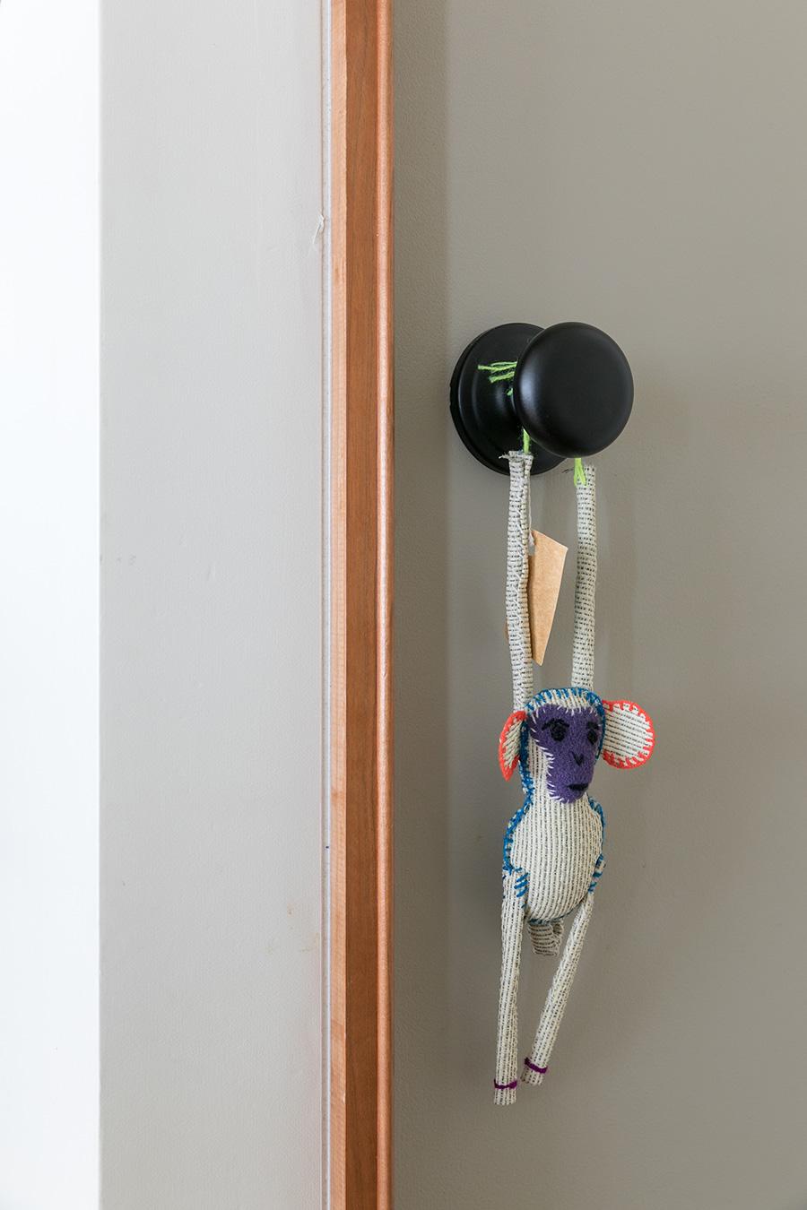 リビング入り口のグレーに塗装した建具。ドアノブにはお気に入りの人形を。