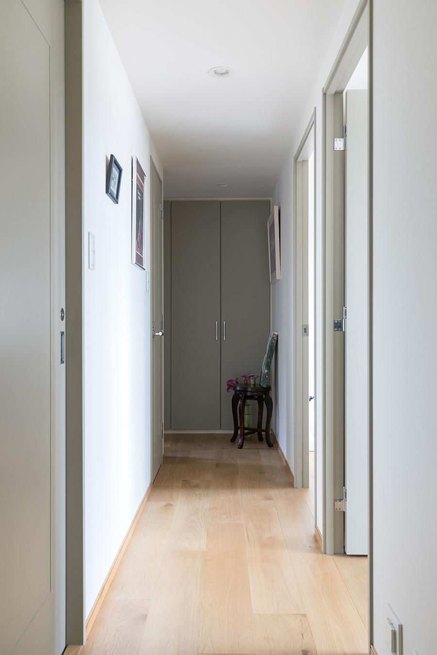廊下もフローリングの明るい木の色合いと建具のグレーが相まって落ち着きのあるシンプルさ。