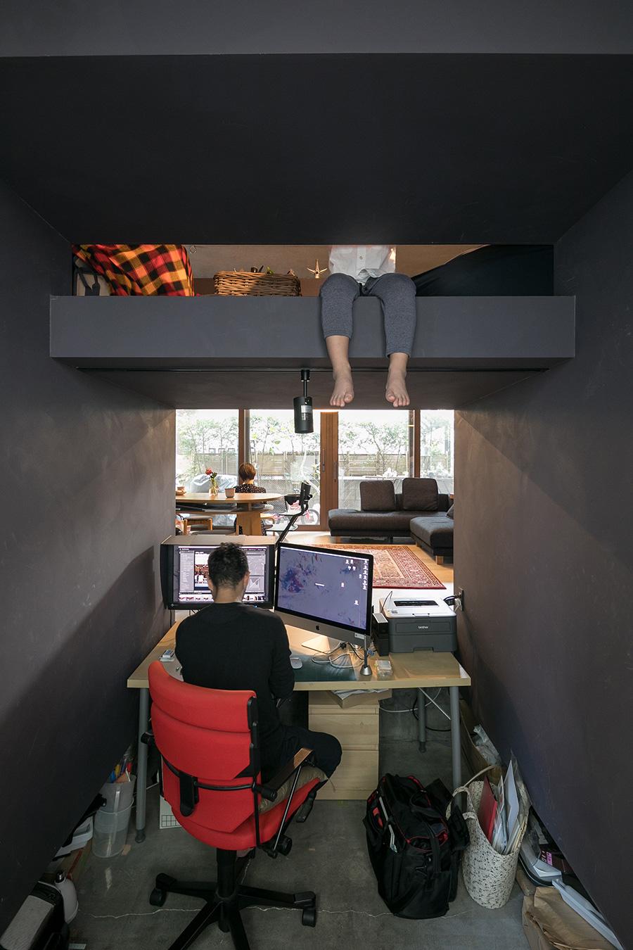 リビングの一部を掘り下げて仕事部屋に。こんな自由な設計を楽しめるのもコーポラティブハウスならでは。上から足を覗かせているのは箱の上階の住人、開くん。仕事スペースの足元には撮影機材を入れられる工夫も。