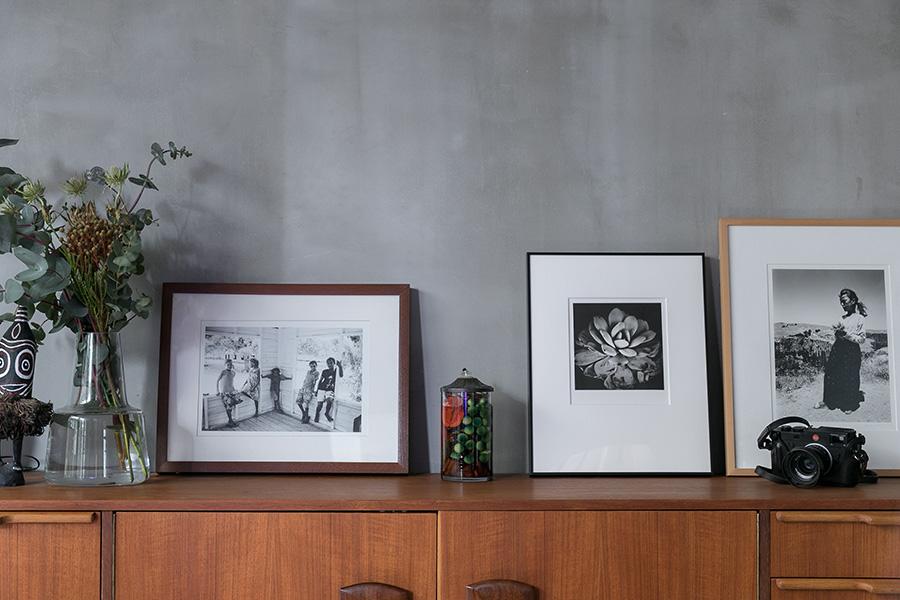 サイドボードの上には植物や写真を飾って。左の2枚は隆弘さんの作品。右は舞山秀一さん。