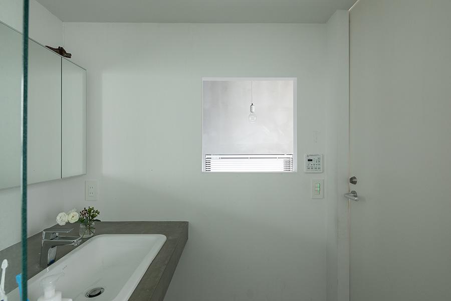 メゾネットタイプの本浪宅。洗面所とバスルーム、ベッドルームは2階にある。正方形の窓から、階段の照明が切り取られた絵のように見える。