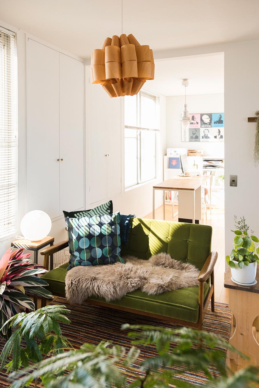 カリモクのソファーは識史さんのお気に入り。照明作家・谷俊幸さんの桜の木のペンダントライトがグリーンに調和する。壁の収納は外に張り出した独特の造り。