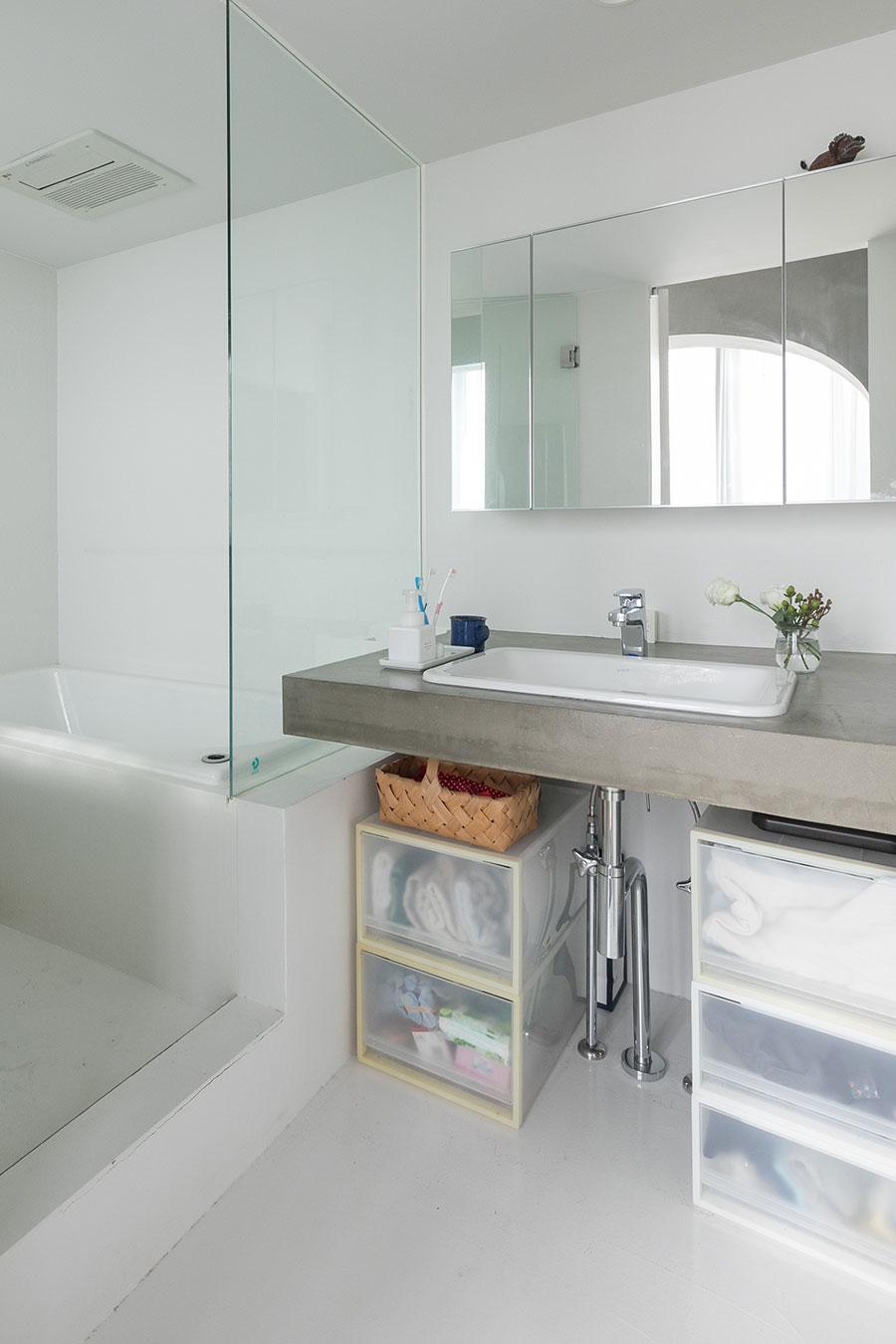 バスルームは白と洗面台のモルタルのグレーの空間。鏡の奥は物入れになっている。
