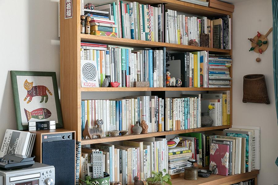 ぎっしりと詰まった本棚の隙間には、小さな人形や郷土玩具など愛着のあるものを置いて。