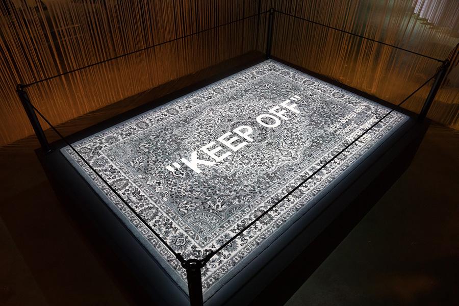 """美術館の立入禁止のロープが貼られている中に収められた作品のように飾られたラグには、""""KEEP OFF""""……立入禁止の文字。"""