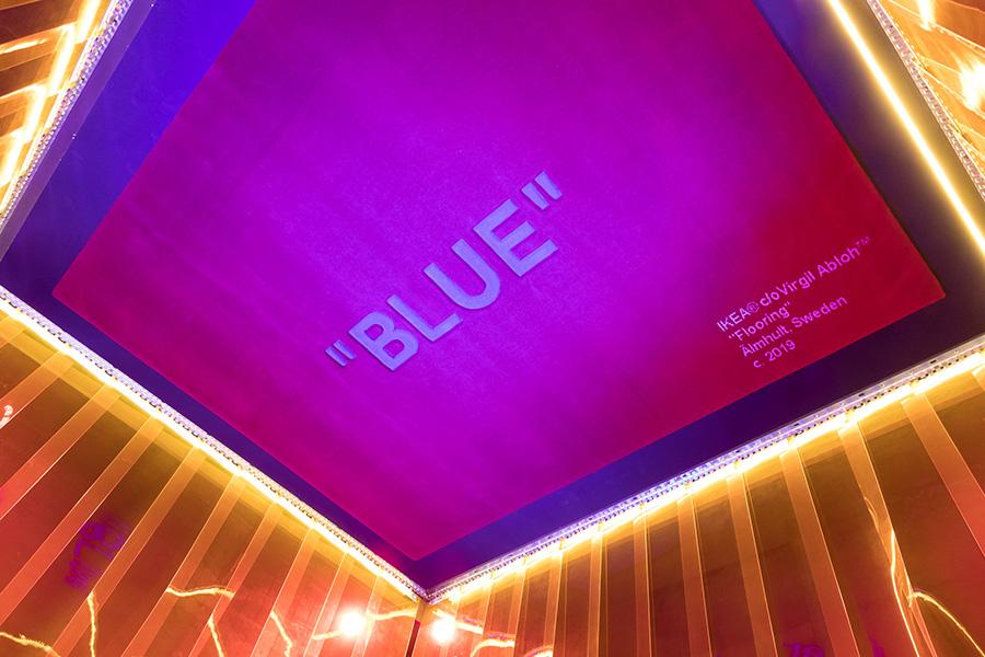 赤いラグに、青(BLUE)の文字。『STILL LOADING』の展示では、さらに鏡に写して鏡文字にしていた。