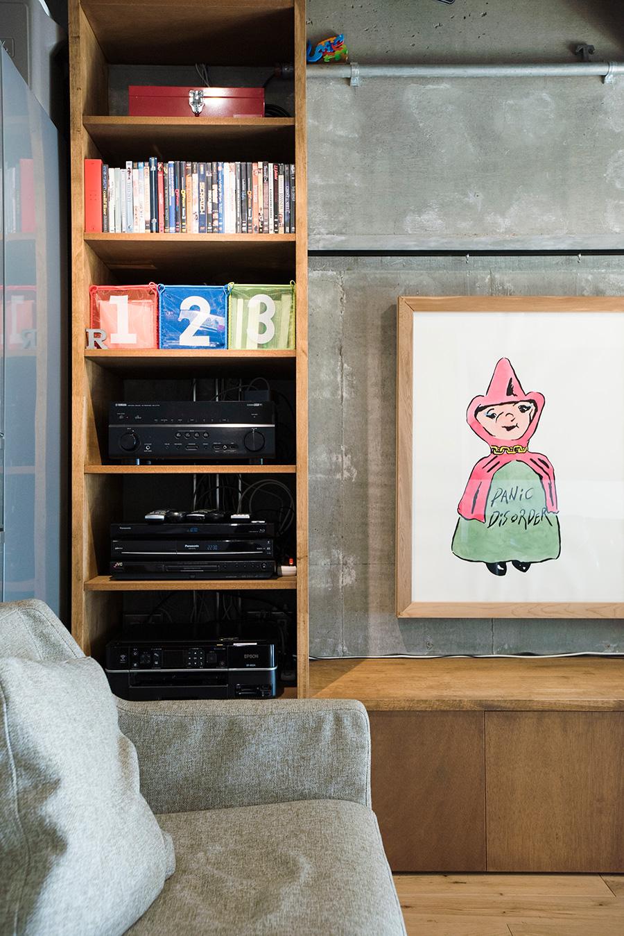 中に収めるもののサイズを細かく計り造作した棚。壁にはアーティスト我喜屋位瑳務の作品を飾る。