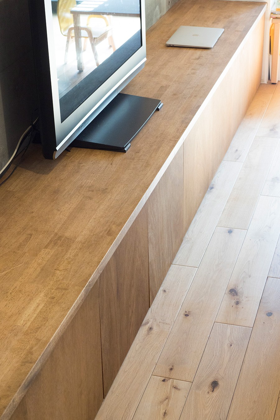 リビングを貫く横長の棚も、縦の棚と同じ素材で造作。集成材にオイルステインを塗り、自然な雰囲気に仕上げてもらった。