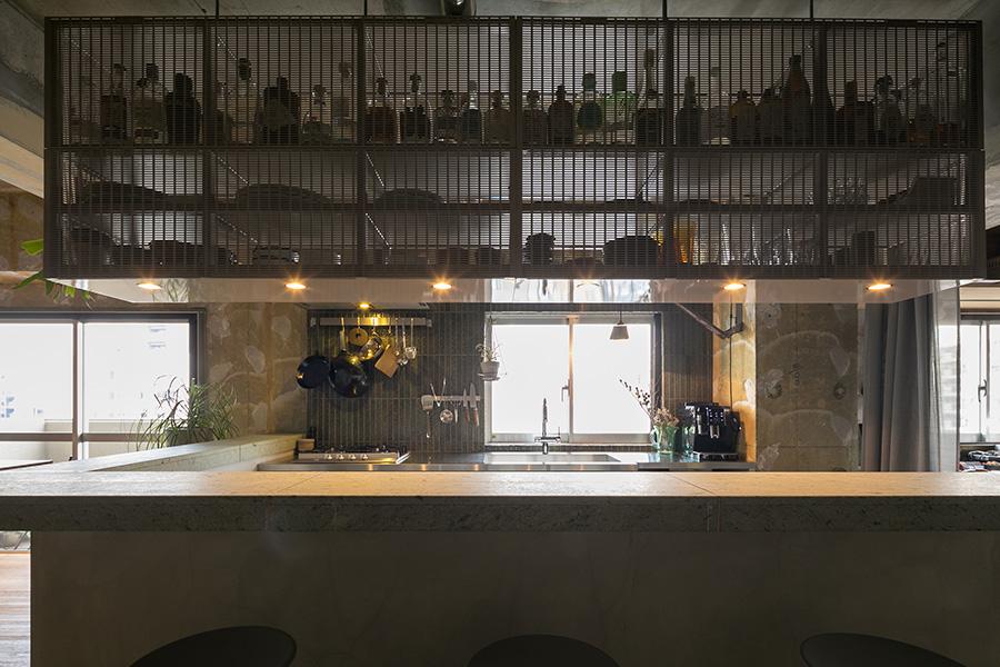 キッチン周りの十和田石のカウンターには真鍮の見切りを入れている。パンチングメタルパネルの奥に並ぶのは永澤さんの趣味で集めているさまざまなジンの瓶。
