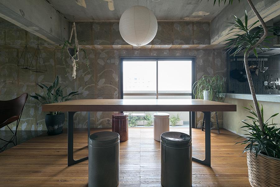 ダイニングテーブルはWOOD WORKに特注したもの。割れの入ったナラの無垢一枚板に、knofでデザインした脚をつけた。陶器の椅子はNOTA&designのオリジナル。照明はイサム・ノグチ。