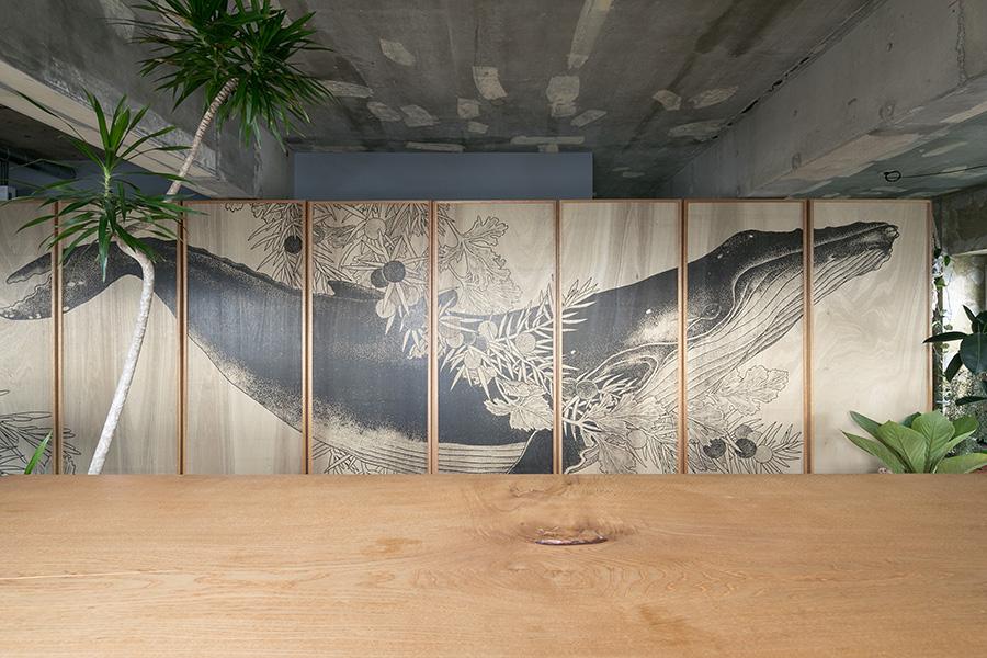 全部で9枚の建具に渡ってプリントされているザトウクジラの絵。鯨に添えられた植物はジンに使われるジュニパーベリーやコリアンダー、ローズマリーなど。長手にあるモチーフが部屋の奥行きを感じさせる。