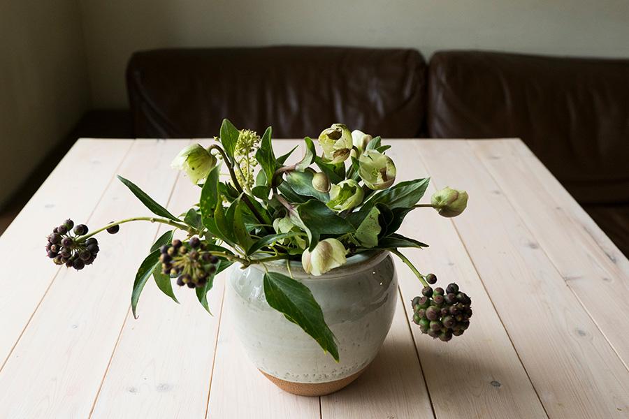 ②中央にクリスマスローズを活けていきベースをつくる。だんだんと花瓶の口をせばめていくつもりで。