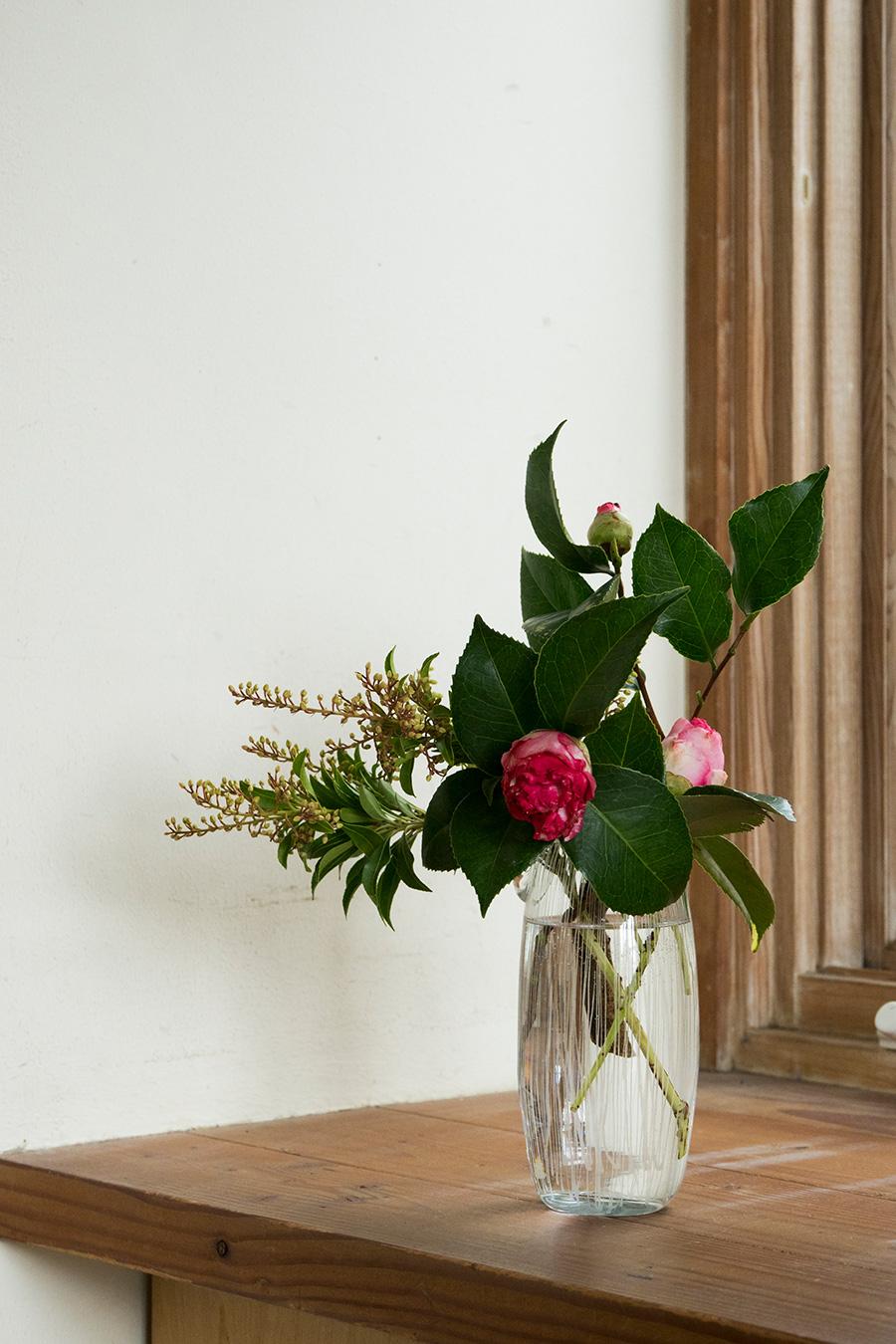 日本原産のツバキは、土ものの器と合わせると和の雰囲気に偏りがち。ガラスの花瓶に活けてクールに表現してみては。