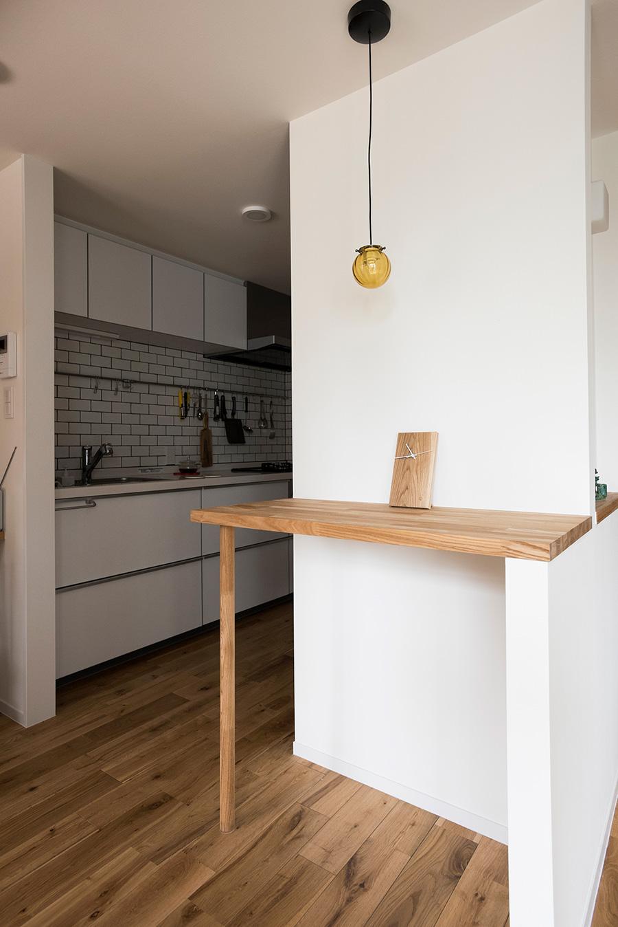 キッチンの脇にタモ材の天板で配膳台を設置。ここで食事をとることもできて便利。