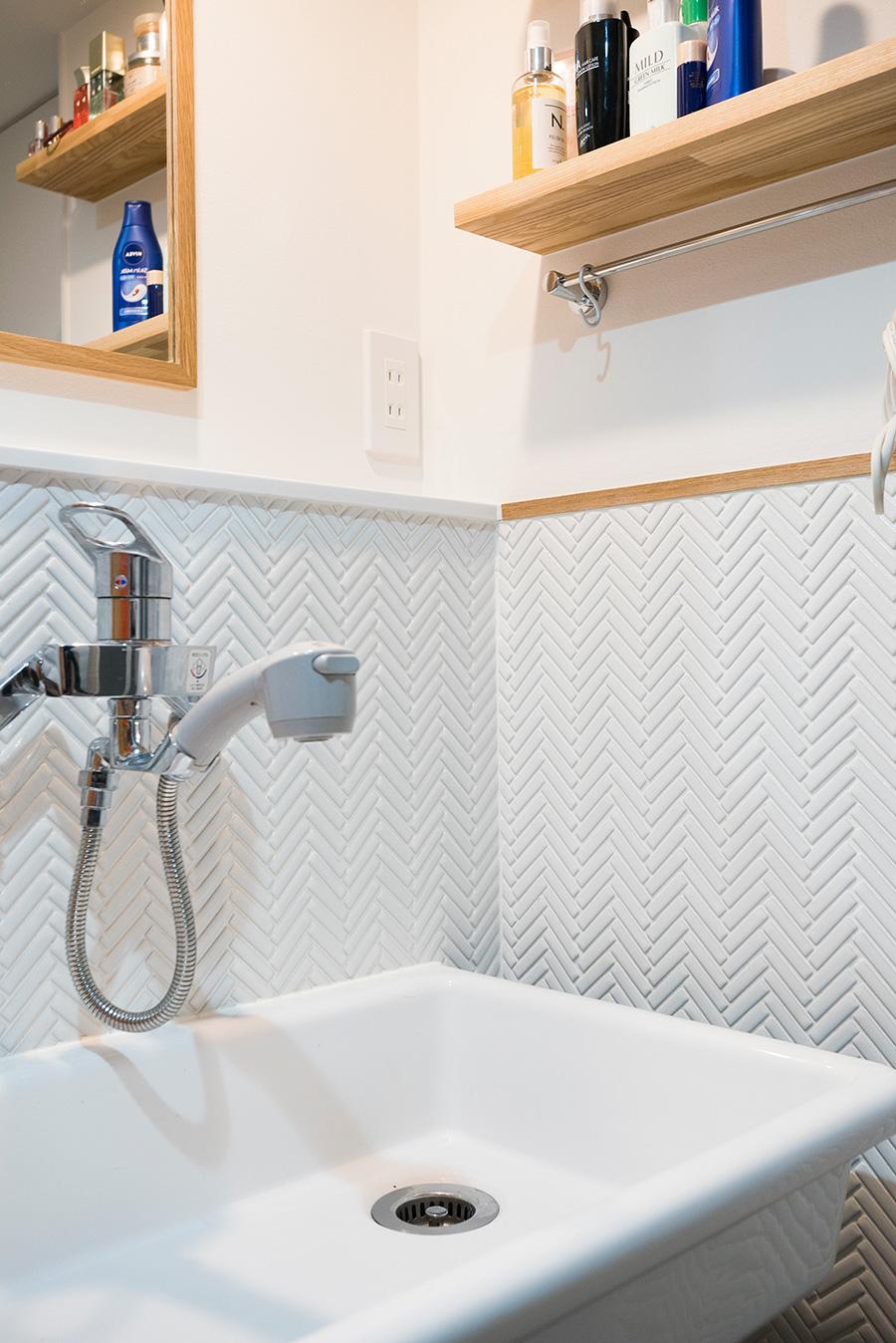 洗面のヘリンボーン貼りのタイルも自らセレクト。職人さんが3日かけて貼ってくれたそう。セーターが手洗いできるよう実験用のシンクに。