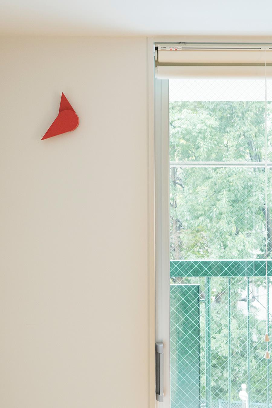 白い空間に窓の外の緑が鮮やかに映える。赤い物体は青山スパイラルで見つけた時計。