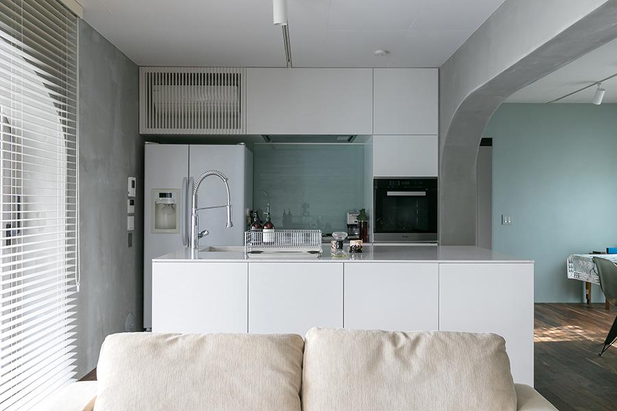 翡翠色の壁とモルタルのグレー、そして真っ白なアイランドキッチンの色のバランスが美しい。レンジの奥の壁はガラスを貼っている。大型の冷蔵庫はGE。