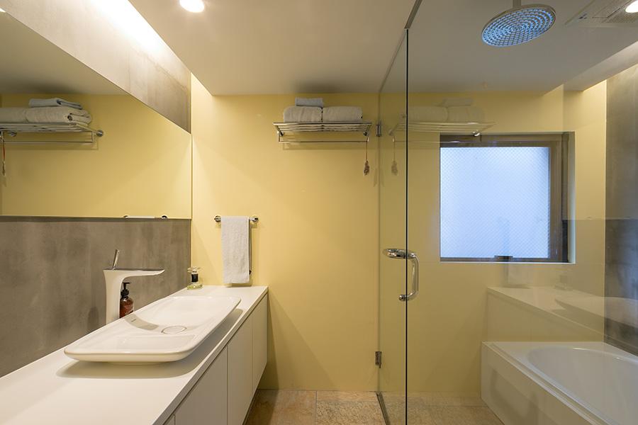 バスルームやトイレなどの水回りの壁はイエローに。DURAVITの洗面ボウル。オーバーヘッドシャワーを採用。