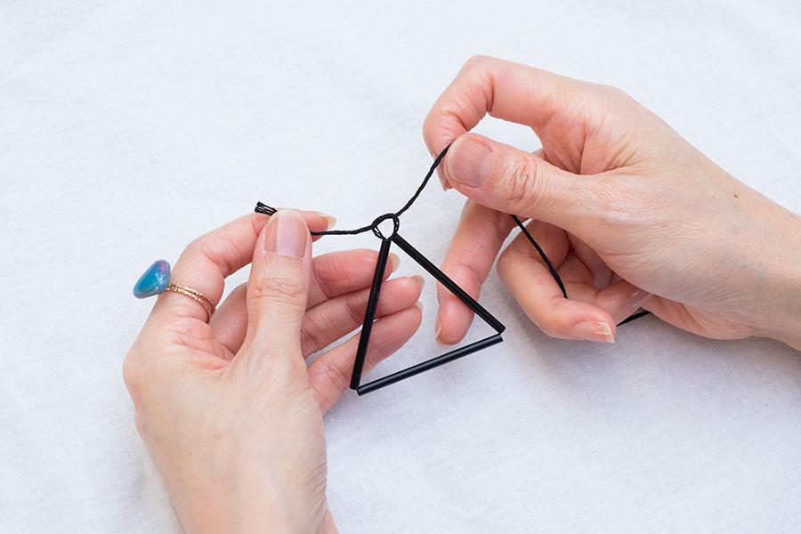 ①ストローは今回5cmにカットしたものを12本用意。片方の糸を5cm程残し、針に糸を通してストローを3本糸に通したら、ストローを合わせて三角形を作って固結び。