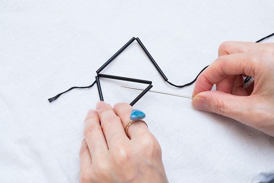 ②さらにストローを2本通し、三角形の下から糸をくぐらせて角に糸を掛け引き締める。