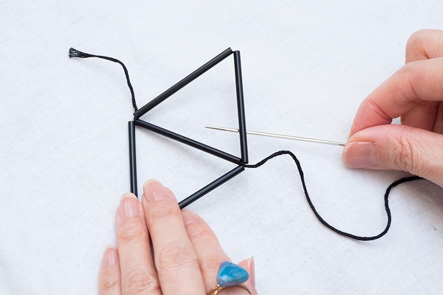 ③新しく作った三角形の下から針を通し、もう一度角に糸をかけて引き締め、ほどけにくくする。