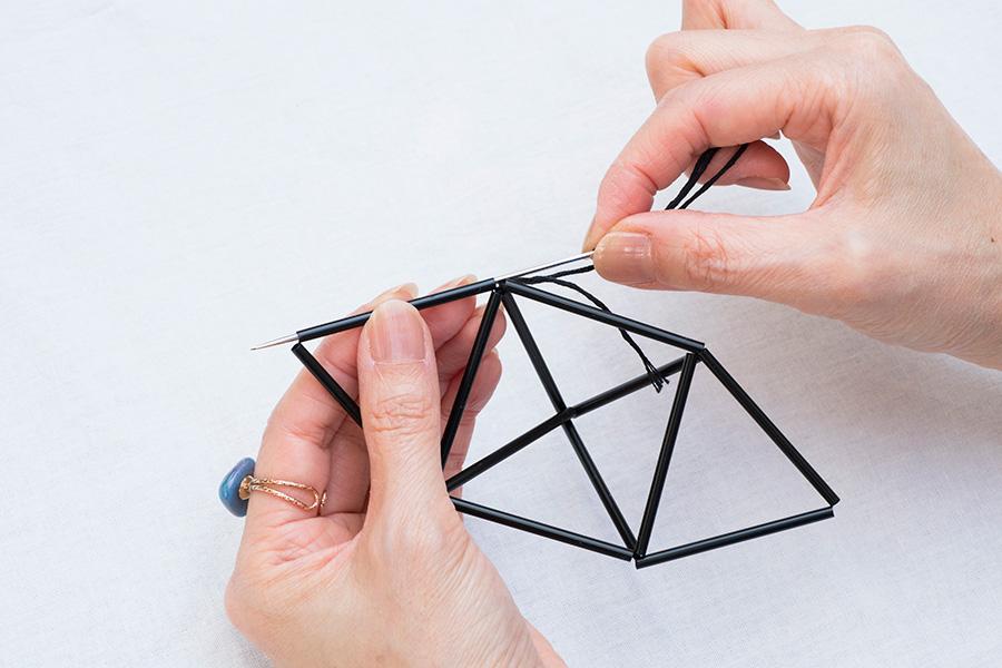 ⑥⑤で固結びをしたところから、いちばん近いところにある三角形の1辺に針をくぐらせて糸を通す。