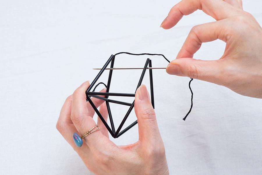 ⑦針を出した三角形と向かいの三角形を内側に起こして合わせ、ふたつの三角形の山の下に、糸を向こう側から通す。