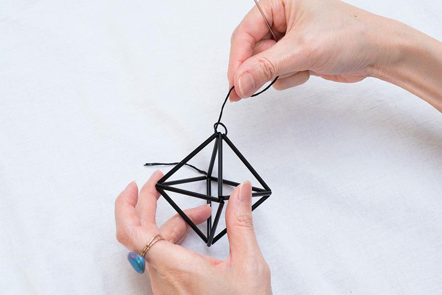 ⑩輪の中心から針を抜き、糸を引き締める。