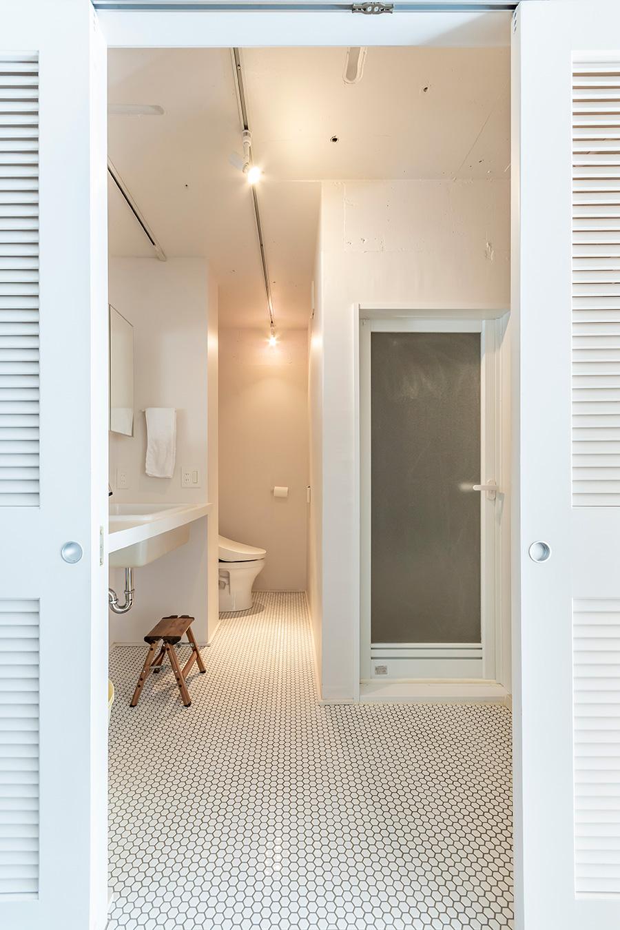 脱衣所の床には丸い白タイルを敷き詰めて。