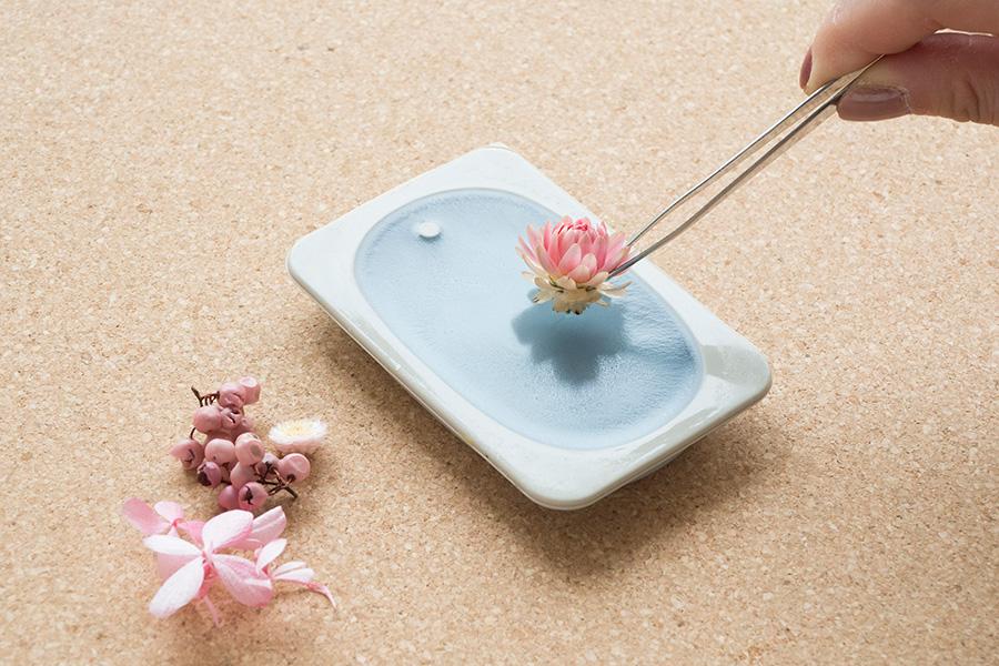 ⑧ワックスの四方が白く固まり、表面に薄い膜が現れたタイミングで、素材を手早く載せていく。