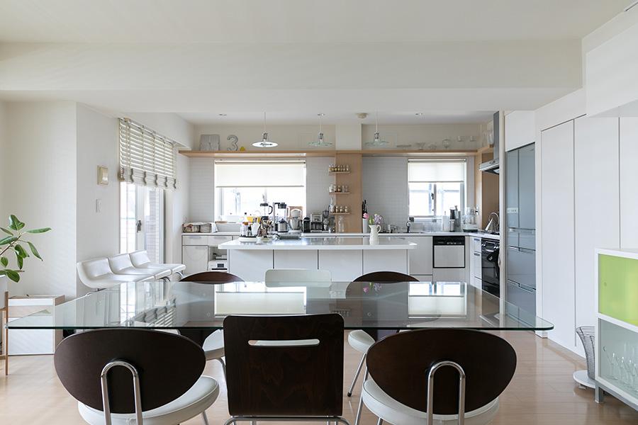リビング側からダイニング・キッチンを見る。ダイニングテーブルは新婚時から長く愛用。「この住まいに合わせ、ガラス天板を大きいものに取り替えました」。
