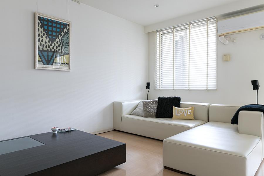 リビングスペースには、空間を圧迫しないローテーブルと白いソファをチョイス。絵画は田上允克氏の作品。「六本木のIDEEで開催された個展に行って、夫婦揃って一目惚れしました」。